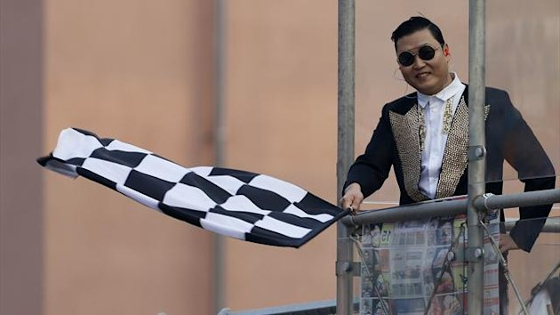South Korea singer Psy waves the chequered flag to Formula One drivers finishing the South Korean F1 Grand Prix at the Korea International Circuit in Yeongam October 14, 2012 (Reuters)