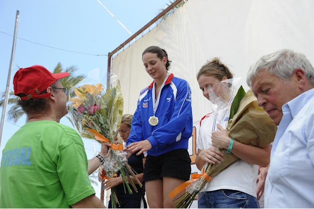 Keri Anne Payne (C) receives a gold medal an a bouquet of flowers after winning the European Open Water Swimming Cup tournament held in the southern Israeli Red Sea port of Eilat on May 7, 2011. AFP P