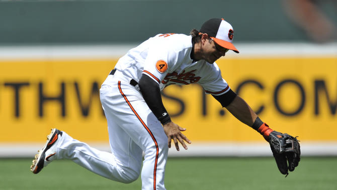 Baltimore Orioles second baseman Brian Roberts reaches for a ground ball hit by Toronto Blue Jays Maicer Izturis in the fourth inning of a baseball game, Sunday, July 14, 2013, in Baltimore. (AP Photo/Gail Burton)