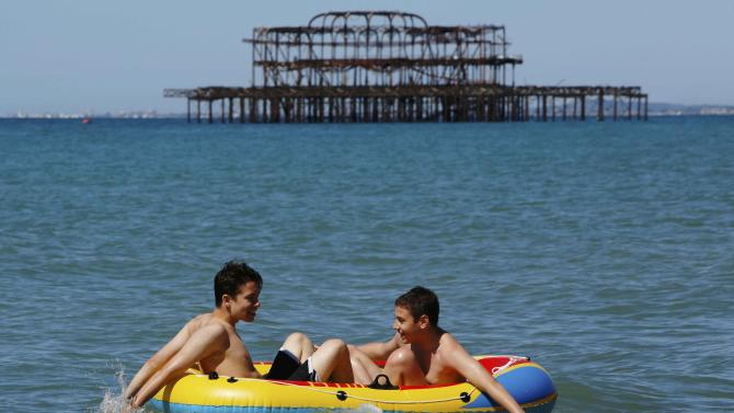 Brothers Balazs Hegedus and Patrick Pataki sit in an inflateble dingy as they paddle in the sea on a hot Summer day at Brighton beach