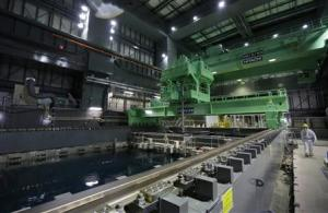 A worker walks next to a fuel handling machine on the spent fuel pool inside the No. 4 reactor building in Fukushima