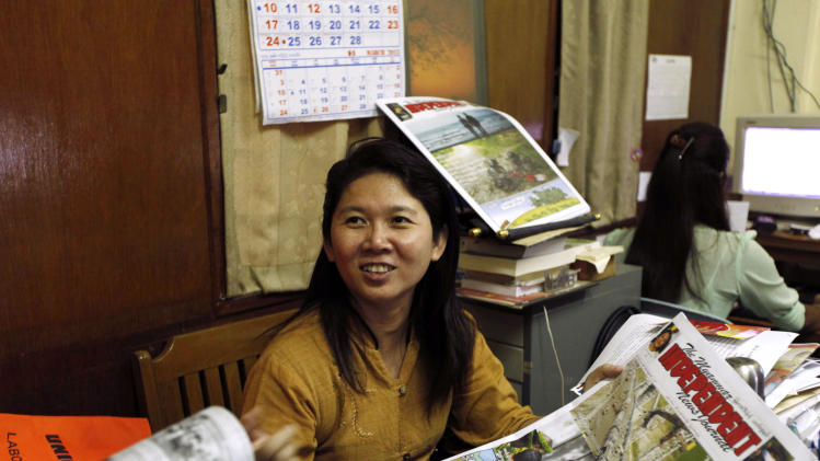 In this photo taken on Thursday, Jan. 31, 2013, author Ma Thida holds a newspaper while talking during an interview at her office in Yangon, Myanmar. Nearly two years into reformist president Thein Sein's term, the rush of hope and idealism that greeted many new freedoms - most strikingly freedom of speech - is turning into a measured assessment of the country's progress. Long accustomed to writing around censorship, Myanmar's writers are relearning the habits of free thought and testing the boundaries of speech.  (AP Photo/Khin Maung Win)