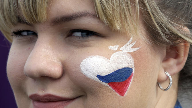 A visitor to Olympic Park wears a painted heart on her face in the colors of the Russian flag on Valentine's Day at the 2014 Winter Olympics, Friday, Feb. 14, 2014, in Sochi, Russia. (AP Photo/David J. Phillip )