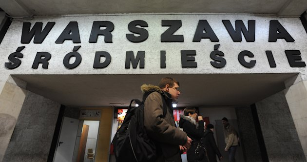 People walk under a board with the name of a train station with several Polish diacritical marks, in Warsaw, Poland, Thursday, Feb. 21, 2013. Polish language experts have launched a campaign, as part