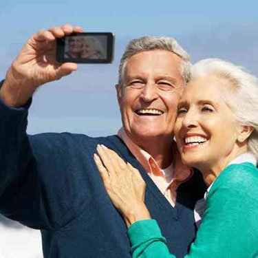 Senior-couple-with-camera-on-beach_web