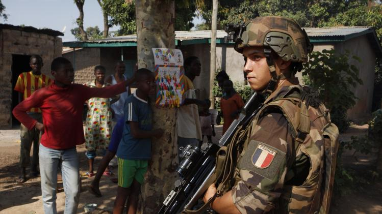 A French soldier stands guard near residents in Bangui