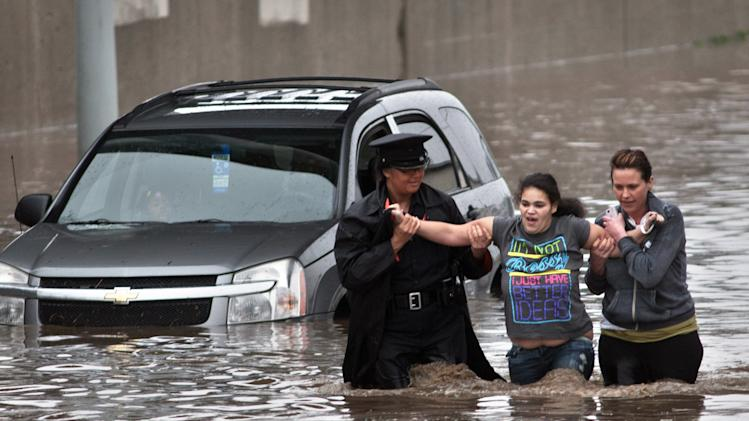 Police officer Shannon Vandenheuvel, left, and Melissa Kolenda, right, help Barbara Jones from her partially submerged car in Grand Rapids, Mich. Thursday, April 18, 2013. Middle America was getting everything nature has to throw at it on Thursday, from snow in the north to tornadoes in the Plains, and with torrential rains causing floods and transportation chaos in several states. (AP Photo/Grand Rapids Press, Chris Clark)