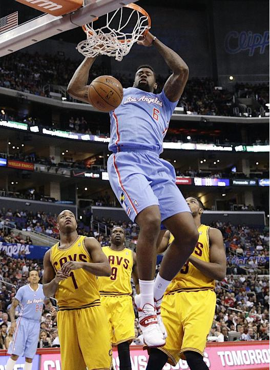 Los Angeles Clippers's DeAndre Jordan, top, makes a dunk as Cleveland Cavaliers's Jarrett Jack, left, and Tristan Thompson, right,  watch during the first half of an NBA basketball game on Sun