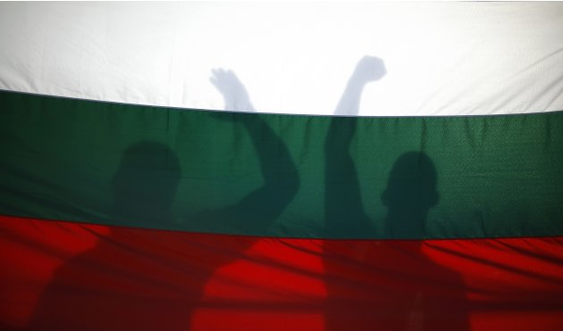 Protesters cast their shadows on a Bulgarian flag as they shout anti-government slogans during a demonstration in central Sofia