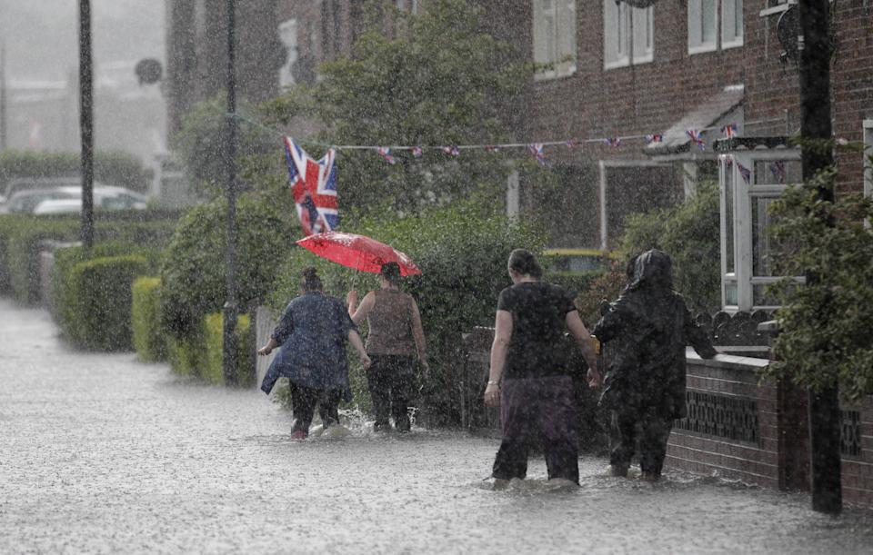 Residents make their way through the flooded streets during heavy rainfall in the Cregagh estate in East Belfast, Northern Ireland, Wednesday, June 27, 2012. (AP Photo/Peter Morrison)