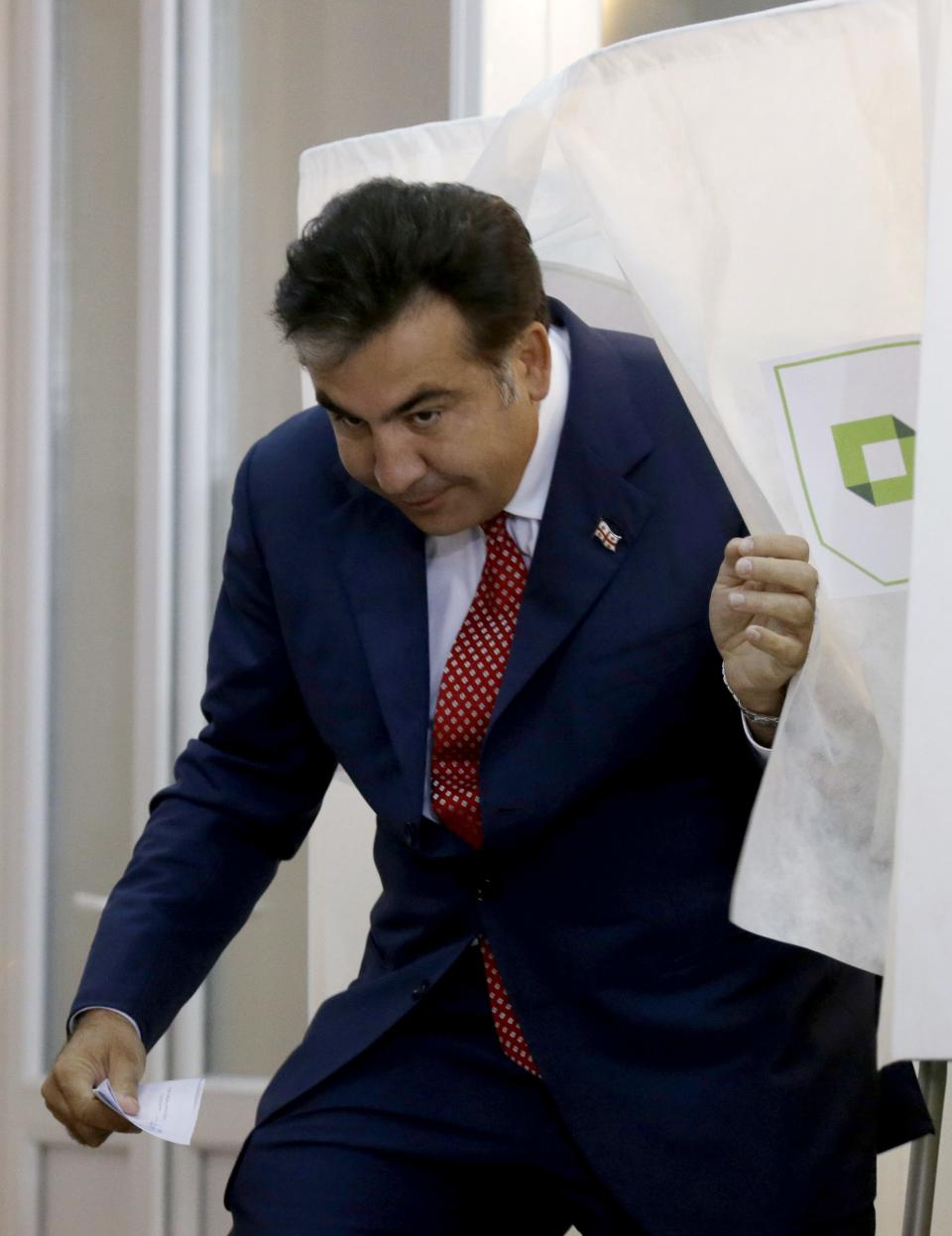 Georgian President Mikhail Saakashvili leaves a voting booth at a polling station in Tbilisi, Georgia, Monday, Oct. 1, 2012. Voters in Georgia are choosing a new parliament in a heated election Monday that will decide the future of Saakashvili's government. (AP Photo/Efrem Lukatsky)