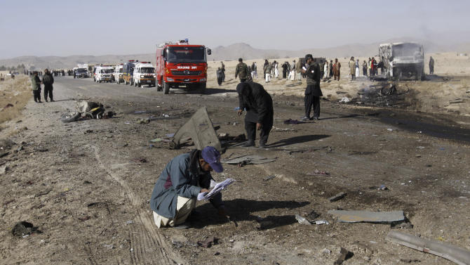 Pakistani police officers, collect evidence from the site of a suicide bombing in Quetta, Pakistan, Sunday, Dec. 30, 2012. A suicide bomber driving a vehicle packed with explosives rammed into a bus carrying Shiite Muslim pilgrims in southwest Pakistan on Sunday, killing several people, a government official and eyewitnesses said. (AP Photo/Arshad Butt)