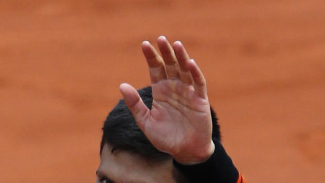 Novak Djokovic of Serbia reacts after beating Thanasi Kokkinakis of Australia during their men's singles match at the French Open tennis tournament at the Roland Garros stadium in Paris