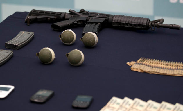 "Confiscated money, grenades, and guns are displayed during the media presentation of the alleged leader of a faction of the hyper-violent Zetas cartel, Ivan Velazquez Caballero, known as ""El Taliban,"""
