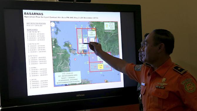 A member of Indonesian National Search and Rescue Agency (BASARNAS) shows a map of searching area on screen during a briefing prior to a search and rescue operation of the missing AirAsia flight QZ8501, at Pangkal Pinang command post, Sumatra Island, Indonesia, Monday, Dec. 29.2014. Search planes and ships from several countries on Monday were scouring Indonesian waters over which the AirAsia jet disappeared, more than a day into the region's latest aviation mystery. Flight 8501 vanished Sunday in airspace thick with storm clouds on its way from Surabaya, Indonesia, to Singapore.(AP Photo/Tatan Syuflana)