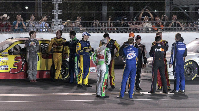 Race leader Dave Blaney, second from left, talks with Landon Cassill, left, as other drivers gather during a red flag in the NASCAR Daytona 500 auto race at Daytona International Speedway in Daytona Beach, Fla., Monday, Feb. 27, 2012. (AP Photo/Bill Friel)