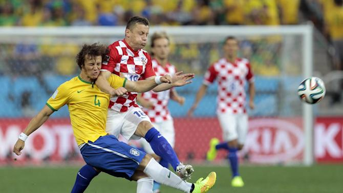 Brazil's David Luiz collides with Chile's Gonzalo Jara during the group A World Cup soccer match between Brazil and Croatia, the opening game of the tournament, in the Itaquerao Stadium in Sao Paulo, Brazil, Thursday, June 12, 2014