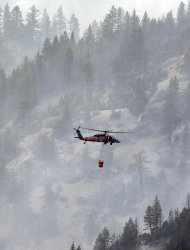 Fire crews prepare to drop water onto the Ponderosa Fire from a helicopter near Mineral, Calif., Thursday, Aug. 23, 2012. The Ponderosa Fire was 57 percent contained, with full containment expected early next week. (AP Photo/Marcio Jose Sanchez)