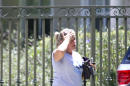 An unidentified woman walks towards the home of the family of journalist Steven Sotloff, Tuesday, Sept. 2, 2014 in Pinecrest, Fla. An Internet video posted online Tuesday purported to show the beheading by the Islamic State group of Sotloff, who went missing in Syria last year. (AP Photo/Wilfredo Lee)