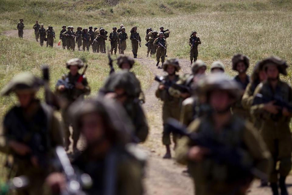 Israeli soldiers march during a military exercise in the Israeli controlled Golan Heights, near the border with Syria, Tuesday, May 7, 2013. (AP Photo/Ariel Schalit)