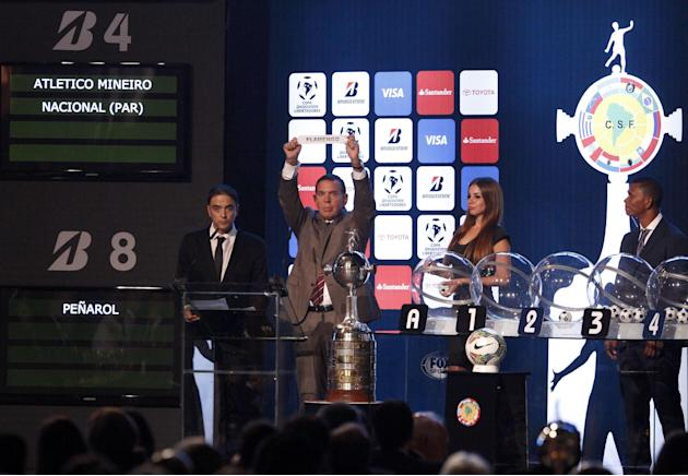 Conmebol's first vice President Juan Angel Napout, second from left,  holds up the name of Brazil's soccer club Flamengo during the draw ceremony for the 2014 Copa Libertadores soccer tourname