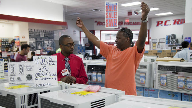 Bernard Gaines, right, describes how wide his window is as he shops for an air conditioner with the help of salesman Leon Blackwood at P.C. Richard & Son, an electronics and appliance store, Tuesday, June 19, 2012 in the Brooklyn borough of New York. Temperatures are expected to approach or top 100 degrees Wednesday and Thursday in cities including New York, Philadelphia and Boston. (AP Photo/Mark Lennihan)
