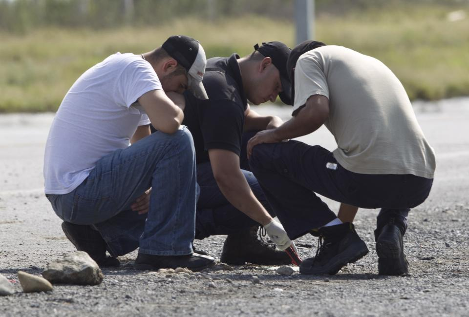 Forensic experts examine the area where dozens of bodies, some of them mutilated, were found on a highway connecting the northern Mexican metropolis of Monterrey to the U.S. border in the town of San Juan near the city of Monterrey, Mexico,  Sunday, May 13, 2012. (AP Photo/Christian Palma)
