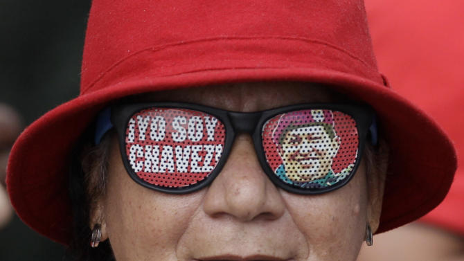 "A supporter of Venezuela's President Hugo Chavez wears glasses that reads in Spanish ""I am Chavez"" while attending a demonstration commemorating the anniversary of a failed coup attempt led by Chavez in 1992, in Caracas, Venezuela, Monday, Feb. 4, 2013. The president was absent for the first time from the annual demonstrations as crowds gathered for multiple marches wearing the red T-shirts of his socialist movement. Chavez remained in Cuba, where he has been out of sight and hasn't spoken publicly since he underwent cancer surgery on Dec. 11. (AP Photo/Ariana Cubillos)"