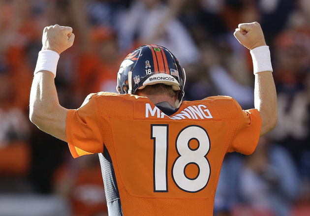 Denver Broncos quarterback Peyton Manning (18) reacts after throwing a touchdown pass to Denver Broncos defensive tackle Mitch Unrein (96) against the Tampa Bay Buccaneers in the first quarter of an N