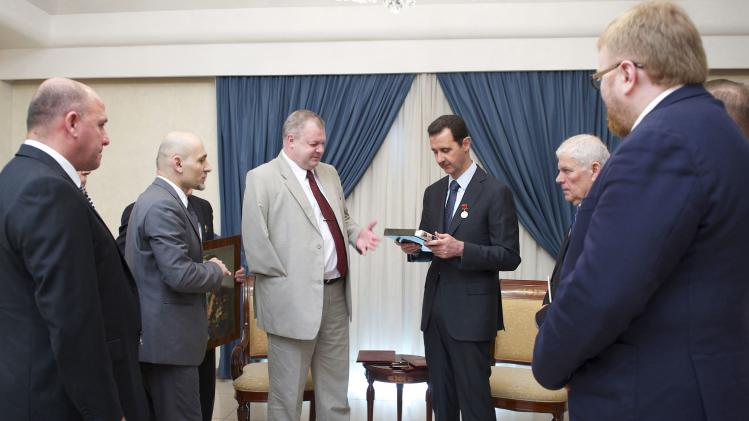 Syria's President Bashar al-Assad receives a gift from a Russian parliamentary delegation during a meeting in Damascus