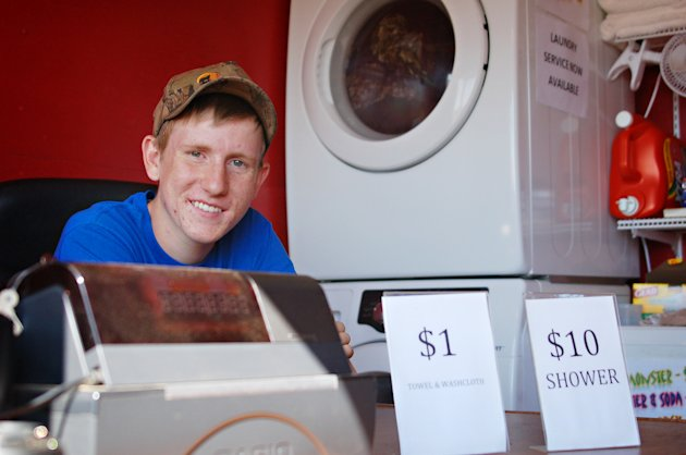 In this Thursday, Aug. 23, 2012 photo, Evan Jensen waits for customers at his mobile shower business, Better Showers, near Alexander, N.D. Jensen raised money for the facility, which caters largely to workers in North Dakota's oil patch, by trapping muskrats and hopes profits from the business will pay for his college tuition. (AP Photo/James MacPherson)