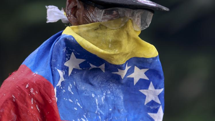 An anti-government protester is draped with a Venezuelan flag during riots at Altamira square in Caracas