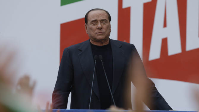 """Silvio Berlusconi talks to his supporters during a demonstration organized by PDL party for its leader, in front of his residence in Rome, Italy, Sunday, Aug. 4, 2013. Italy's former premier, Silvio Berlusconi, for the first time in decades of criminal prosecutions related to his media empire was definitively convicted of tax fraud and sentenced to prison by the nation's highest court. Judge Antonio Esposito, in reading the court's decision Thursday, declared Berlusconi's conviction and four-year prison term """"irrevocable."""" He also ordered another court to review the length of a ban on public office — the most incendiary element of the conviction because it threatens to interrupt, if not end, Berlusconi's political career. (AP Photo/Andrew Medichini)"""