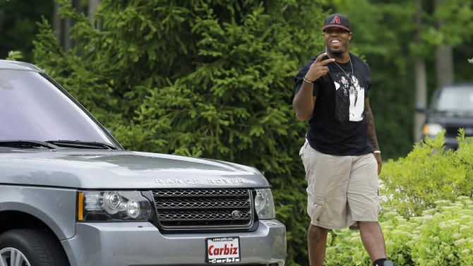Baltimore Ravens linebacker Terrell Suggs gestures to members of the media as he walks into the team's training facility, Wednesday, July 29, 2015, in Owings Mills, Md., to report for NFL football training camp. (AP Photo/Patrick Semansky)