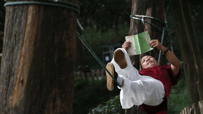 Liang Yanguo reads a book as he lies on a rope tied between two trees, as a form of martial arts practice, at a park in Huangyan district of Taizhou, Zhejiang province