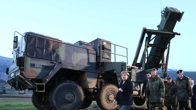 German Chancellor Angela Merkel  walks past a  Patriot  defense  system during her visit to  Kahramanmaras, southeastern Turkey Sunday Feb. 24, 2013. German Chancellor Angela Merkel is visiting German troops deployed to operate Patriot missile batteries in Turkey. The Patriots were sent to Turkey, a NATO member, to protect it from spillover from Syria's civil war. Merkel's two-day visit comes as Turkey grows increasingly frustrated over the slow progress in its bid for European Union membership. Before arriving Sunday, Merkel said she backs opening a new chapter in those stalled talks, despite being skeptical about Turkey's accession.  The chancellor's first stop was Kahramanmaras, some 100 kilometers (60 miles) from the Syrian border, where some 300 German troops are manning two out of six NATO-deployed anti-missile batteries.  (AP Photo/dpa,Kay Nietfeld)