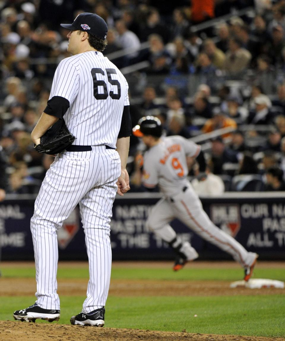 New York Yankees starting pitcher Phil Hughes (65) reacts as Baltimore Orioles' Nate McLouth, right, runs the bases after hitting a home run during the fifth inning of Game 4 of the American League division baseball series on Thursday, Oct. 11, 2012, in New York. (AP Photo/Bill Kostroun)
