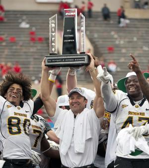 Southern Mississippi head coach Larry Fedora, center, raises the Conference USA Championship trophy with Ryan Balentine (80) and Nic Bekkers, right, after an NCAA college football game against Houston, Saturday, Dec. 3, 2011, in Houston. Southern Mississippi defeated Houston 49-28. (AP Photo/Dave Einsel)