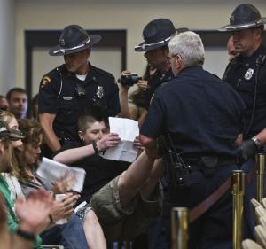 A protester is removed from a meeting of the Joint Committee on Finance at the state Capitol Friday, June 3, 2011, in Madison, Wis. Wisconsin's Republican lawmakers re-opened the fight over collective bargaining rights Friday, proposing new police and firefighters pay more for their health insurance and pension benefits. (AP Photo/Morry Gash)