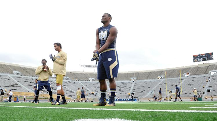 Players loosen up on the new turf prior to an NCAA college football game between Notre Dame and Rice in South Bend, Ind. Saturday Aug. 30, 2014