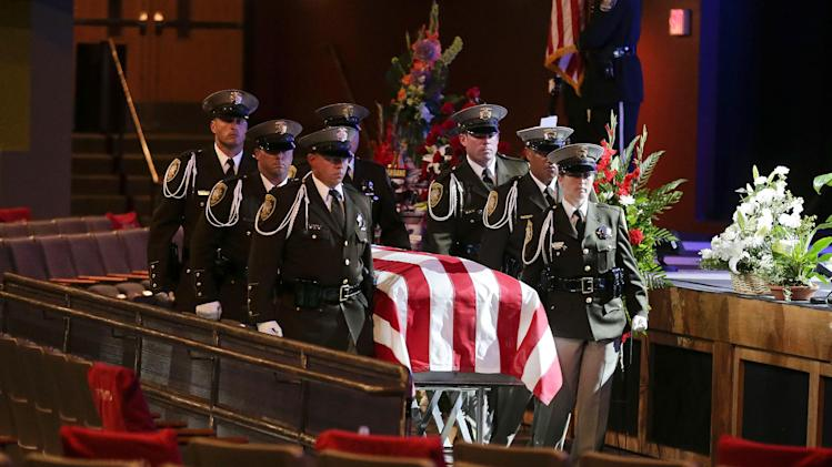 Las Vegas Metro Police officers roll the flag-draped casket of search and rescue officer David Vanbuskirk to its place inside Central Christian Church before a funeral service, Monday, July 29, 2013, in Henderson, Nev. Vanbuskirk fell to his death attempting to rescue a stranded hiker on a rocky ledge at Mount Charleston on July 22. Vanbuskirk's death marks the first time a Las Vegas officer has died on duty since 2009. (AP Photo/Julie Jacobson)