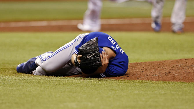 Toronto Blue Jays starting pitcher J.A. Happ reacts after being hit in the head with a line drive off the bat of Tampa Bay Rays' Desmond Jennings during the second inning of a baseball game Tuesday, May 7, 2013, in St. Petersburg, Fla. (AP Photo/Mike Carlson)