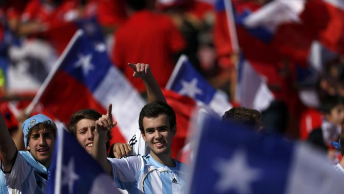 Argentina fans cheer amid a sea of Chilean flags as they await the start of the Copa America 2015 final soccer match between Argentina and Chile at the National Stadium in Santiago