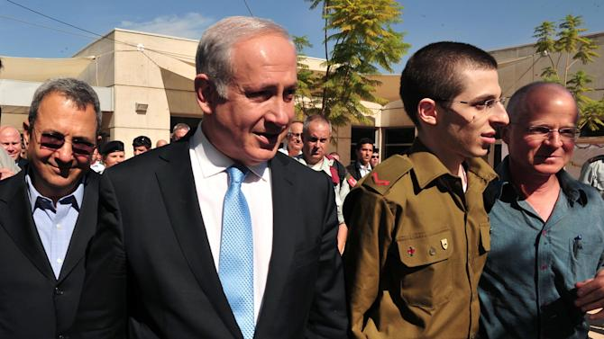 In this photo released by the Israeli Defense Ministry, released Israeli soldier Gilad Schalit, second right, walks with his father Noam, right, Israeli Prime Minister Benjamin Netanyahu, second left, and Defense Minister Ehud Barak, left, at the Tel Nof Air base in southern Israel, Tuesday, Oct. 18, 2011. Looking thin, weary and dazed, an Israeli soldier returned home Tuesday from more than five years of captivity in the Gaza Strip in exchange for hundreds of Palestinian prisoners whose joyful families greeted them with massive celebrations. (AP Photo/ Defense Ministry, Ariel Hermoni, HO)  EDITORIAL USE ONLY:
