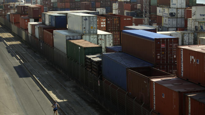 A man runs past containers placed at Lisbon's Santa Apolonia port, Wednesday, Aug. 14, 2013. Eurostat, the European Union's statistics office, said the 17 EU countries that use the euro saw their collective economic output increase by 0.3 percent in the April to June period from the previous quarter. That's the first quarterly growth since the eurozone slipped into recession in the last three months of 2011. (AP Photo/Francisco Seco)