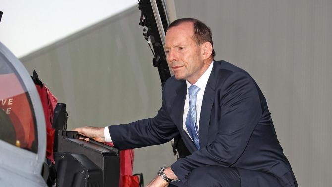 Australia Prime Minister Abbott stands on the wing of a RAAF F/A-18F Super Hornet at RAAF Base Amberley, located near Brisbane, during a ceremony for personnel departing for the UAE