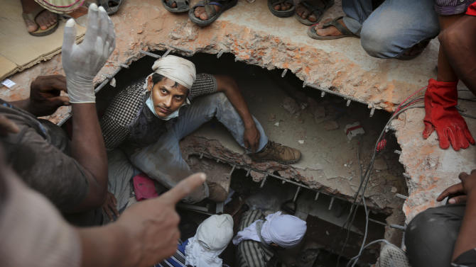 A Bangladeshi rescuer looks out from a hole cut in the concrete as he looks for survivors at the site of a building that collapsed Wednesday in Savar, near Dhaka, Bangladesh, Thursday, April 25, 2013. By Thursday, the death toll reached at least 194 people as rescuers continued to search for injured and missing, after a huge section of an eight-story building that housed several garment factories splintered into a pile of concrete.(AP Photo/Kevin Frayer)