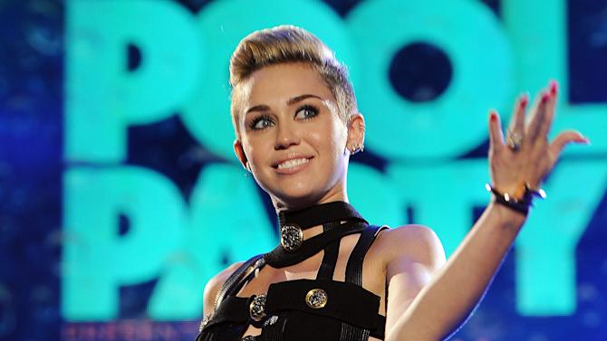 "FILE - This June 29, 2013 file photo shows Miley Cyrus hosting the iHeartRadio Ultimate Pool Party at the Fontainebleau Hotel in Miami. NBC said Monday, Sept. 9, that the singer and actress, who popularized the word ""twerking"" and found new uses for foam fingers during an attention-getting duet with Robin Thicke on the MTV Video Music Awards last month, will be both host and musical guest of the NBC late-night program on Oct. 5. (Photo by Jeff Daly/Invision/AP, File)"