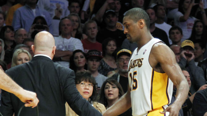 Los Angeles Lakers trainer Gary Vitti, left, escorts Metta World Peace from the court after he was ejected for double flagrant fouls against the Oklahoma City Thunder in the first half of an NBA basketball game in Los Angeles, Sunday, April 22, 2012. The Lakers won in double overtime, 114-106. (AP Photo/Reed Saxon)