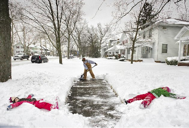 Jason Smith  clears the sidewalk in front of his home at the 2400 block of Anthony Blvd., in Fort Wayne, Ind., before heading to work Wednesday morning March 6, 2013, as his daughters Kylie Smith, rig